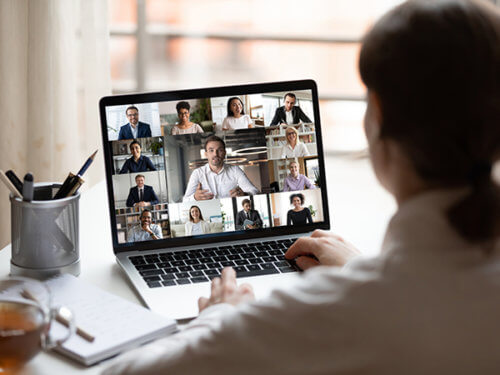 Over-the-shoulder shot of a woman viewing a laptop screen with a photo collage of diverse people