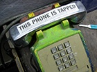 "telephone with sticker that says ""this phone is tapped"""