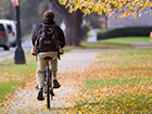 young man bicycling on a university campus