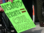 person in wheelchair holding sign saying disability rights equal civil rights