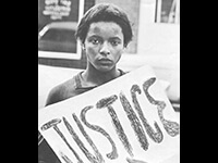 woman holding a sign that reads justice