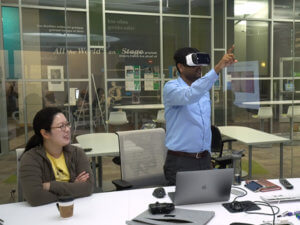 a woman watching a man who is wearing VR glasses and pointing in the air