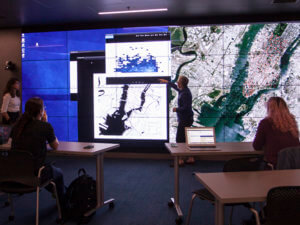 man standing in front of multiple maps displayed on screen on wall
