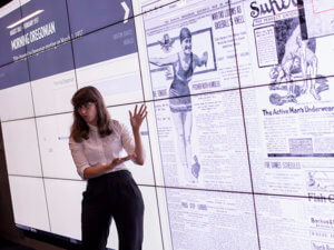 woman standing in front of large screen with historic newspaper displayed on it