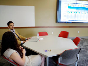 a man and a woman sitting at a table in a study room with a graph projected onto a screen next to them