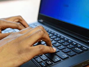 closeup of a man's hands typing on a laptop keyboard