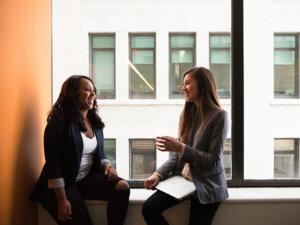 two professional women sitting in a window talking