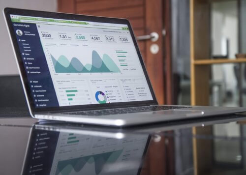 Open laptop showing charts and data.