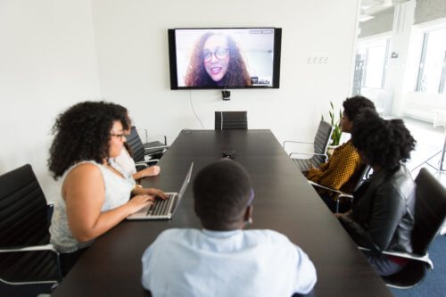 4 people at a conference table videoconferencing with a colleague.