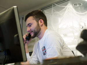 Student worker at computer screen talking on telephone
