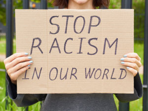 white-person-holding-cardboard-handwritten-sign-saying-stop-racism-in-our-world