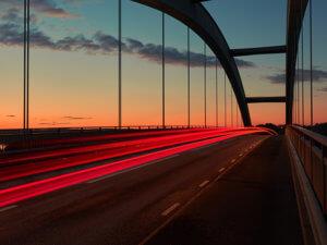 time-lapse photo of sunrise light trails on a bridge