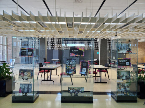 Three glass display cases containing photographs and posters