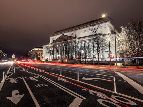 photo of US National Archives building at night with light trails from cars