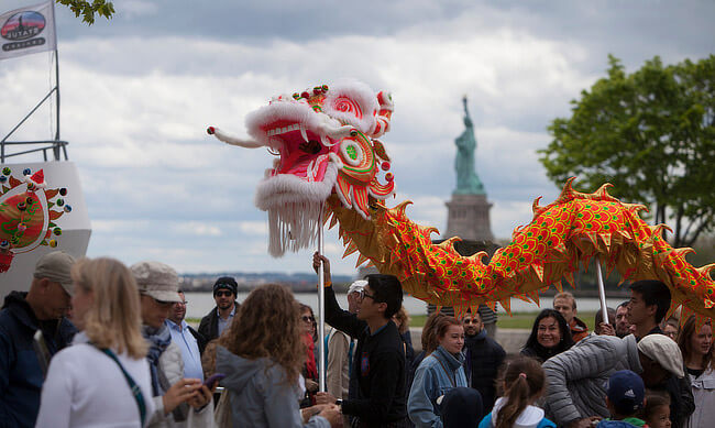 Two people holding up a dragon in a crowd, with the Statue of Liberty in the background