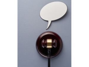 photo of a gavel with a paper cutout of a speech bubble