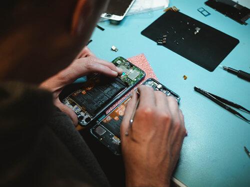 photo of person repairing mobile phone