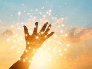 photo of open hand with networked points of light in sunrise