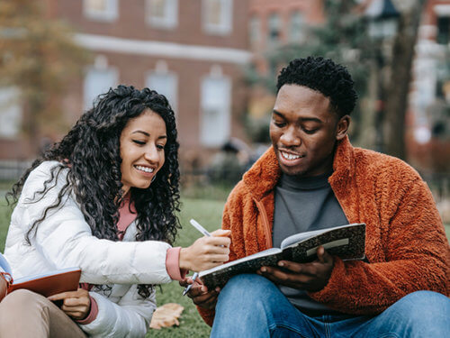 photo of two people of color on campus writing in composition books