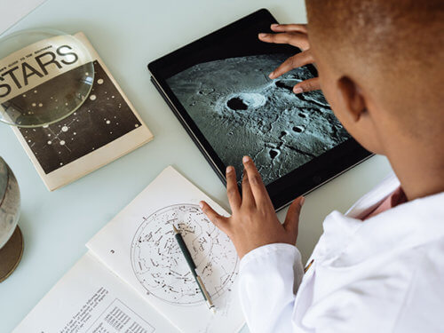 photo of a Black scientist in a lab coat studying moon craters on a tablet computer
